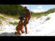 Ett svart par gör sex på stranden
