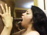 En latina kvinna med en svart kuk i hennes mun