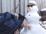 Flickan gör sex med en snögubbe utomhus
